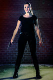 Dangerous woman terrorist dressed in black with a gun in her han. Ds Stock Photo
