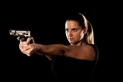 Dangerous woman terrorist dressed in black with a gun in her han Stock Photography