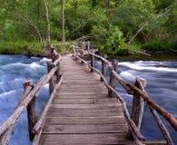 Dangerous Wooden Bridge. A dangerous looking wooden bridge above Oklahoma rapids Royalty Free Stock Images