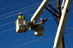 Dangerous Work. Linemen at work installing new utility lines Royalty Free Stock Photo