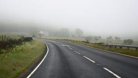 Dangers of driving in fog - road turn. Dangerous driving in fog on turning road, shot in English countryside Stock Image
