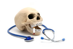 The dangers of smoking. Rubber skull with cigarette and stethoscope to illustrate the dangers of smoking Stock Photography