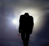 The suitor 2. Black silhouette of a man with red eyes and a red rose in his hand Royalty Free Stock Images