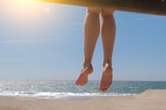 Dangling bare female feet sitting on beach. Sunny day on ocean shore royalty free stock images