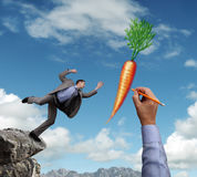 Dangling a carrot. Businessman trying to reach a dangling carrot being drawn in the sky by a giant hand concept for business motivation, incentive, temptation or Royalty Free Stock Images