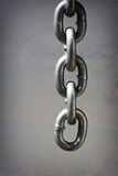 Dangling Chain. A detailed closeup macro of a heavy duty chain dangling in front of a dingy white wall. Room for copy space royalty free stock images