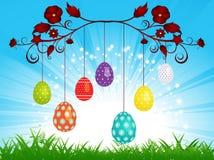 Dangling Easter eggs on blue sky landscape. Easter Eggs and Dangling on a Blue Sky and Grass Stock Images