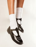 Dangling Girls School Shoes. A dangling set of kids legs with short white socks and black girls school shoes on a white background royalty free stock photo