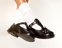 Dangling Girls School Shoes. A dangling set of kids legs with short white socks and black girls school shoes on a white background royalty free stock photos