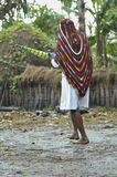 Dani woman in a modern white dress and traditional cap on a head. With umbrella and water. DUGUM DANI VILLAGE, BALIEM VALLEY, IRIAN JAYA, NEW GUINEA, INDONESIA royalty free stock photo