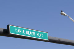 Dania Beach Boulevard Sign. White and green Dania Beach Blvd in Dania Beach, Florida street sign with a bright blue sky in the background. Dania Bach Blvd street royalty free stock images