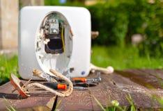 Danificado da corrosão e da oxidação, o aquecedor de água encontra-se no fundo da caldeira em uma tabela de madeira imagem de stock royalty free