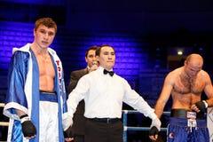 Danil Shved en de tribune van Ioannis Militopulos op boksring Stock Fotografie