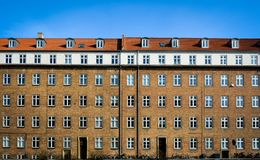 Danish apartment building - brick facade. A classic facade of a multistory apartment building in yellow bricks, red roof tiles and windows with white dividers stock photography