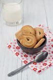 Danish butter biscuits with milk. Danish butter cookies in a brown bowl with milk on a white wooden background Stock Image
