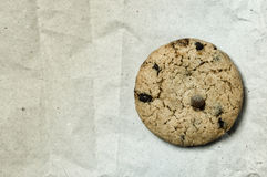 Danish cookie with chocolate. Macro shot of a danish cookie with chocolate drops over a white recycled paper background Royalty Free Stock Image
