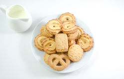 Danish cookies seved with jug of milk   on white backgro Royalty Free Stock Images