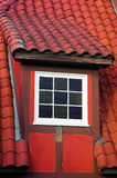 Danish Dormer. A white dormer window in a red Danish building with a tiled roof stock photography