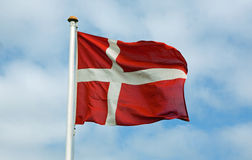 Danish Flag. Against a blue sky with clouds Stock Image