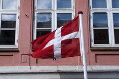 Danish flag. Close to pink building in Bogense in Denmark Stock Images
