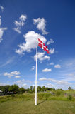 Danish flag. Green nature, blues sky and clouds Royalty Free Stock Image