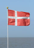 Danish flag. A Danish flag with the sea at the background Royalty Free Stock Photography
