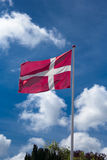 Danish Flag. On a blue bag ground with a few clouds red and white tripes blowing in the wind Royalty Free Stock Photos