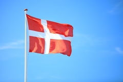 Danish flag with blue sky on background stock photography