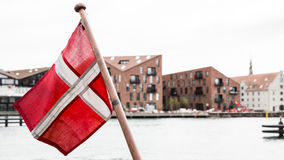 Danish flag. A danish flag with buildings in the background Stock Photos