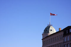 Danish Flag on a cultured building. A danish flag stands tall on top of a cultured building in Central Copenhagen in front of a brilliant clear blue sky Stock Photos