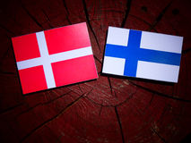 Danish flag with Finnish flag on a tree stump isolated. Danish flag with Finnish flag on a tree stump Royalty Free Stock Photo