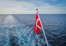 Danish flag hanging from a ship. Danish flag hanging from the stern of a ferry a ship crossing the north sea Royalty Free Stock Photography