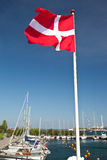 Danish flag and harbour. Bright red Danish flag flying above a boat harbour Royalty Free Stock Images