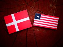 Danish flag with Liberian flag on a tree stump isolated. Danish flag with Liberian flag on a tree stump Stock Images