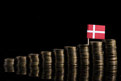 Danish flag with lot of coins isolated on black. Background Stock Photos