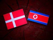 Danish flag with North Korean flag on a tree stump. Danish flag with North Korean flag on a tree stump Royalty Free Stock Image