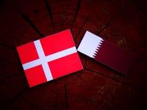 Danish flag with Qatari flag on a tree stump isolated. Danish flag with Qatari flag on a tree stump Royalty Free Stock Photo