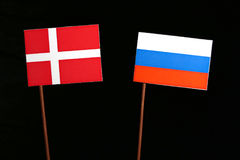 Danish flag with Russian flag isolated on black. Background Royalty Free Stock Image