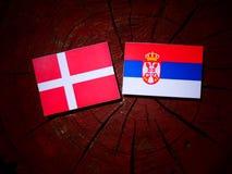 Danish flag with Serbian flag on a tree stump  Stock Photos