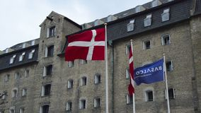 Danish flag waving with the Admiral hotel on the background, Copenhagen, Denmark stock video footage