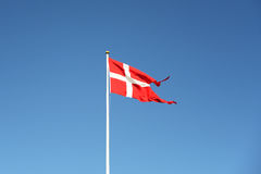 Danish flag waving against blue sky. Red-white flag flying in the clear sky Royalty Free Stock Photo