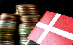 Danish flag waving with stack of money coins. Macro Stock Images