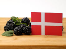 Danish flag on a wooden panel with blackberries isolated on a wh. Ite background Stock Image