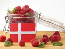 Danish flag on a wooden panel with raspberries isolated on a whi. Te background Royalty Free Stock Photography