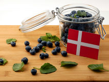 Danish flag on a wooden plank with blueberries  on white. Danish flag on a wooden plank with blueberries Royalty Free Stock Photos