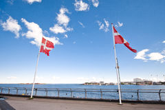 Danish flags against a blue cloudy sky. Danish flags on the shore of the Baltic Sea. Sunny weather. Blue sky with clouds Stock Images