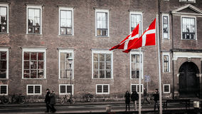 Danish flags in Copenhagen. Nyhavn district is one of the most famous landmarks in Copenhagen with typical colorful houses Royalty Free Stock Images
