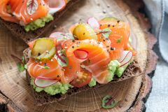 Smorrebrod with salmon on rye bread with vegetables and herbs. Danish open sandwich Smorrebrod with salmon on rye bread with vegetables and herbs Stock Images