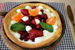 Danish pancake with berries and whipped cream topping. Covered with sugar powder Royalty Free Stock Images