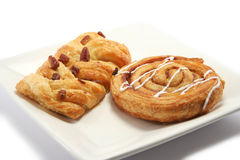 Danish Pastries. Cinnamon Swirl and Maple/Pecan danish pastries on a square plate royalty free stock photo